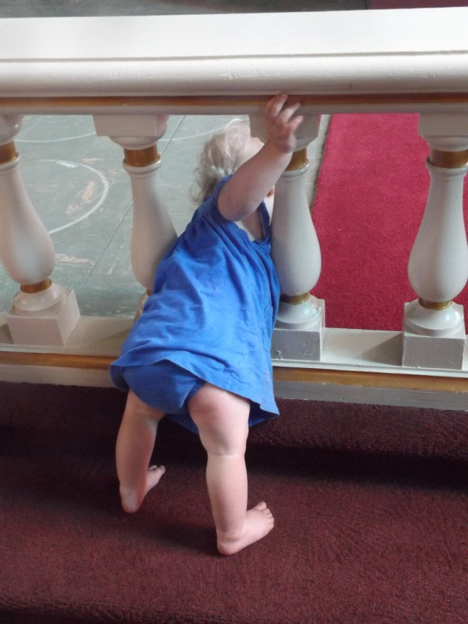 AnaClaire trying to climb through the communion rail.