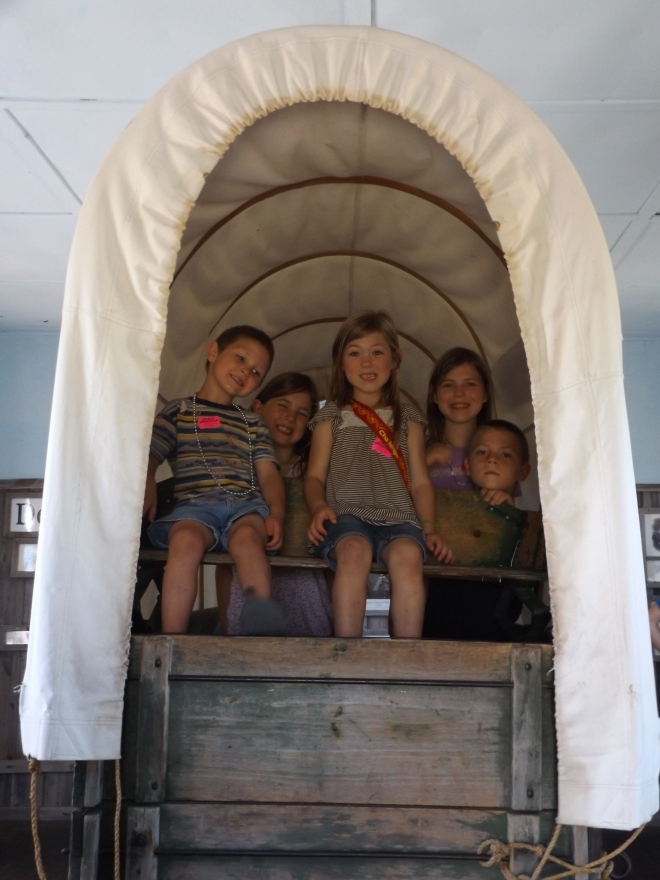 The kids in the back of a covered wagon.