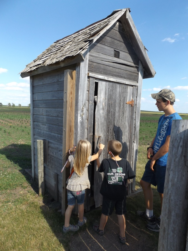 The kids waiting to use the functional, two-seater outhouse.